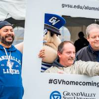 3 alumni pose with Louie and the #GVhomecoming sign